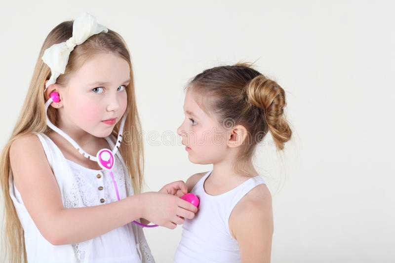 Little girl listens heartbeat of another girl by toy phonendoscope. Little girl in white dress listens heartbeat of another girl by toy phonendoscope and looks royalty free stock image
