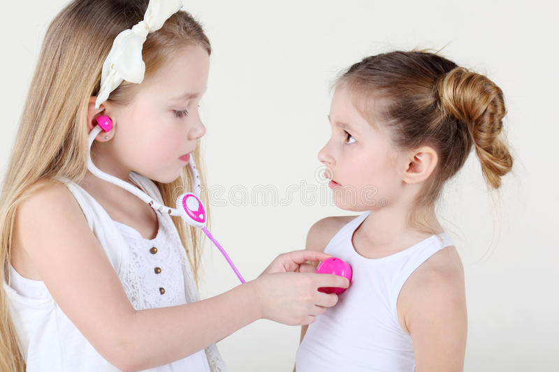 Little girl listens heartbeat of another girl by toy phonendoscope. Little girl in white listens heartbeat of another frightened girl by toy pink phonendoscope stock photo