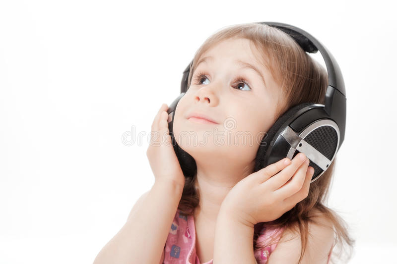 The little girl listens to music stock photo
