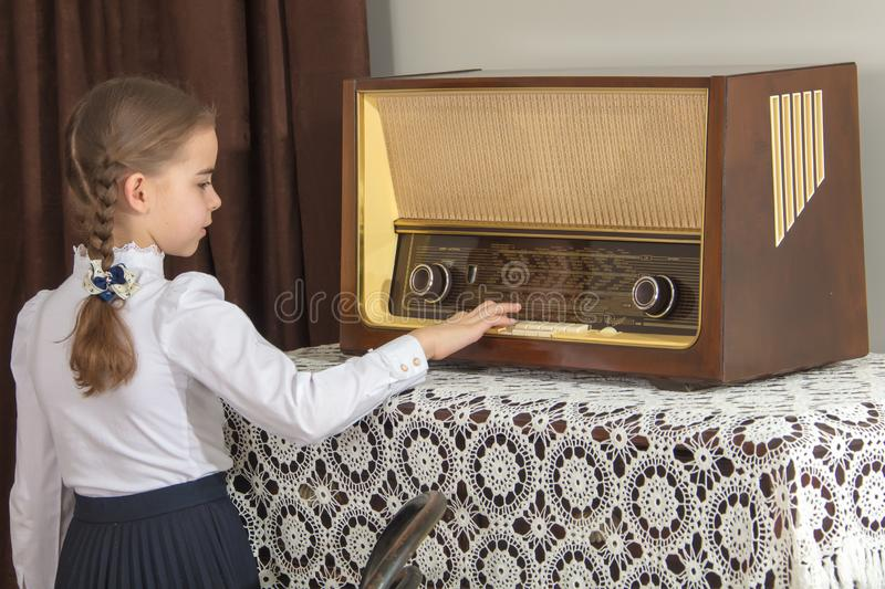 Little girl listens to old radio. royalty free stock photography