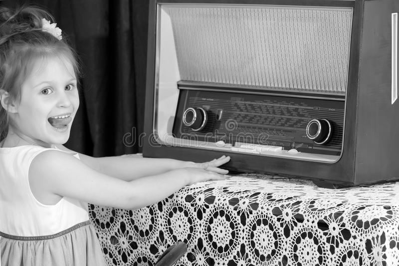 Little girl listens to old radio. stock photography