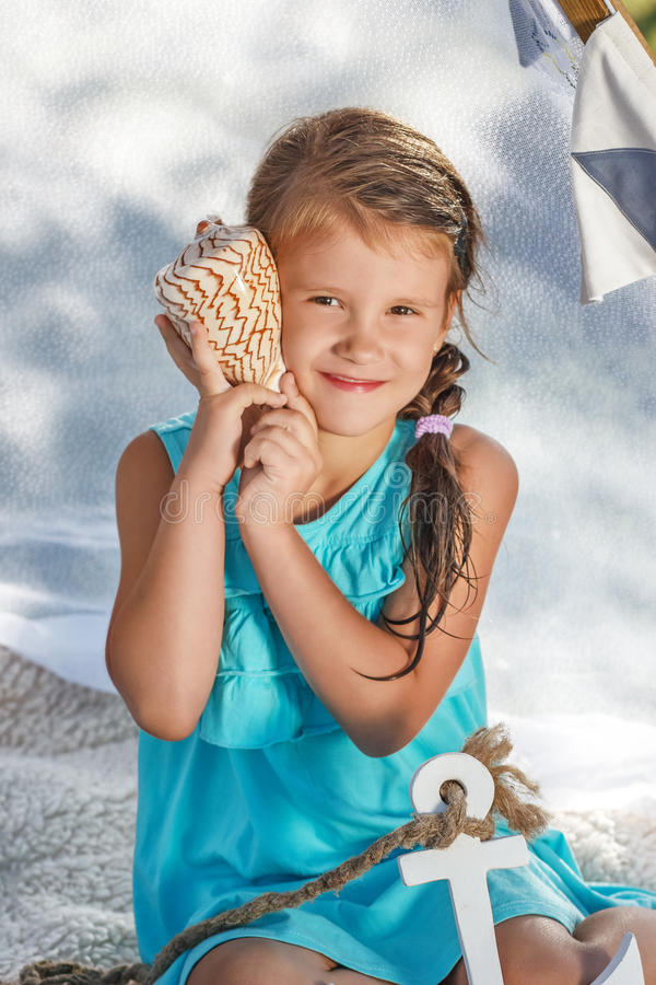 Little girl listens to the sea through the shell royalty free stock image