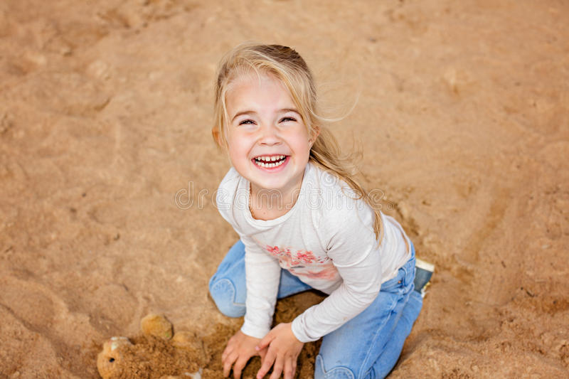 Little girl little girl sitting on the sand on the beach and grins, playing with the sand in the summer stock photo