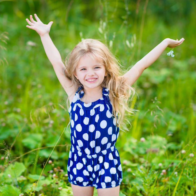 Little girl with long blond curly hair and raised hands. Cute smiling little girl with long blond curly hair and flower in her hands. Girl with raised hands royalty free stock images