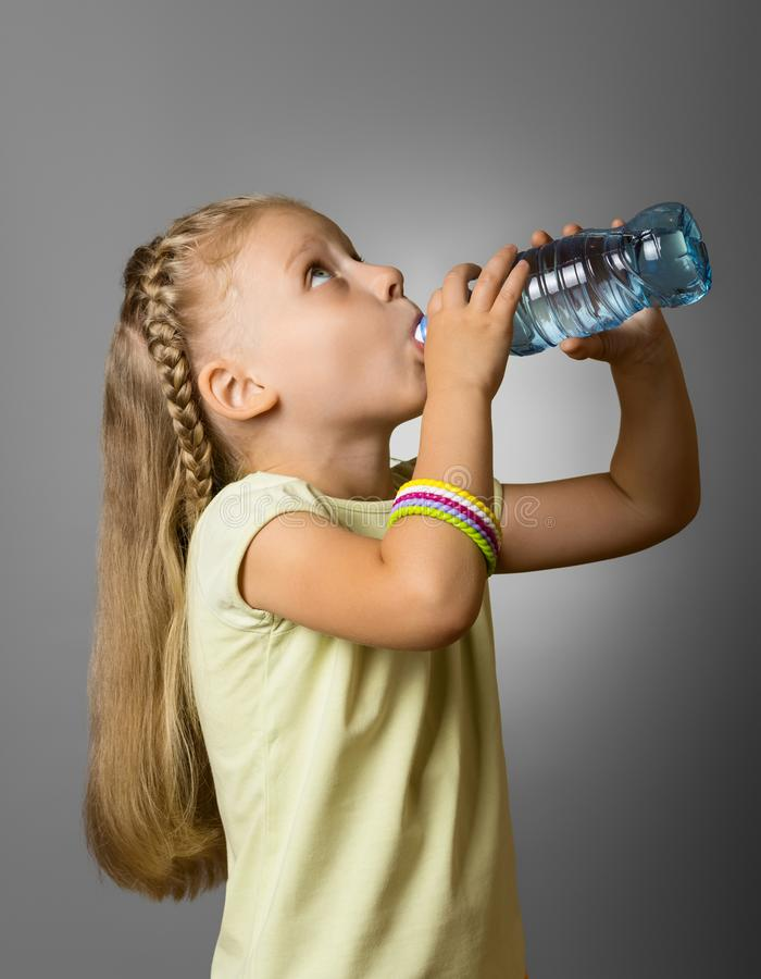 A little girl with long hair, drinking water from plastic bottle on grey. Background stock photos