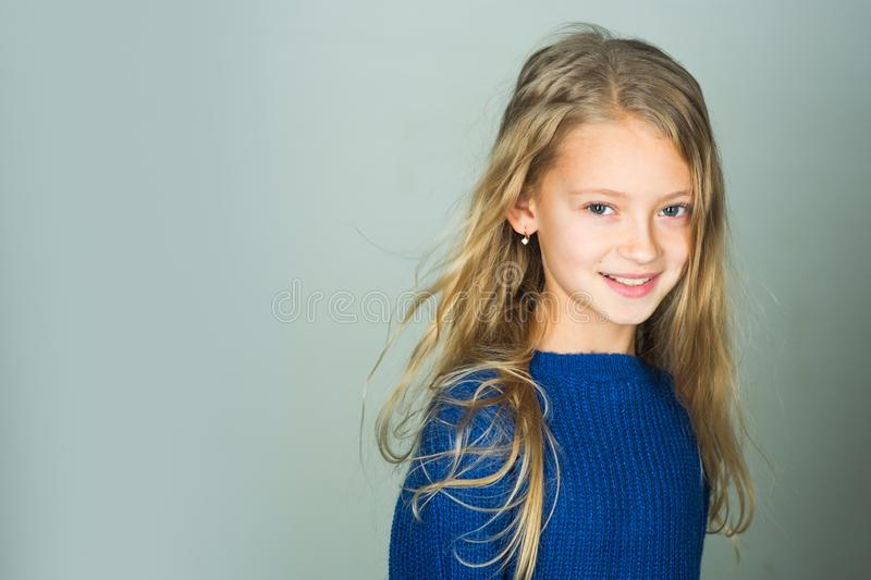 Little girl with long hair. Fashion model, beauty, look. Stylish girl with pretty face on grey background. Hairdresser. Skincare, casual style, denim. Beauty royalty free stock photos
