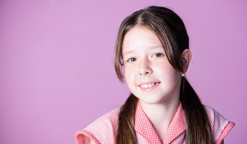 Little girl with long hair. Kid cute face with adorable hair on pink background. Beauty tips for tidy hair. Innocence royalty free stock photography