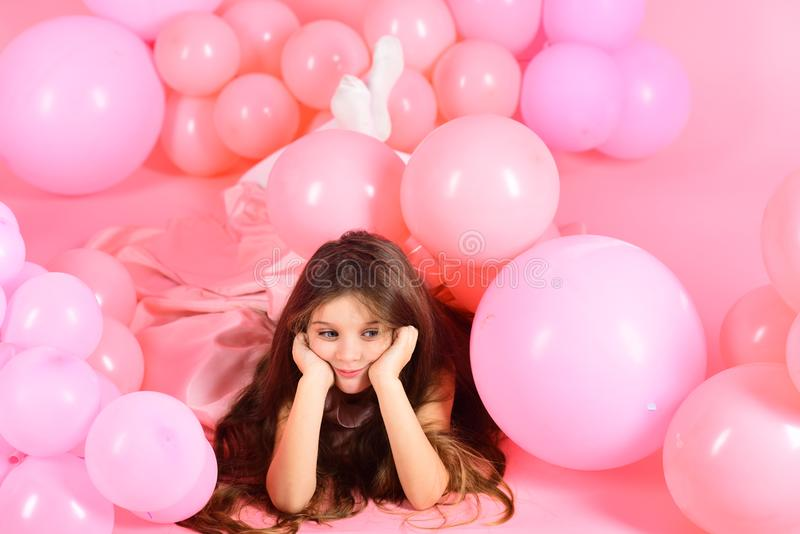 Little girl with long hair in pink balloons. royalty free stock image