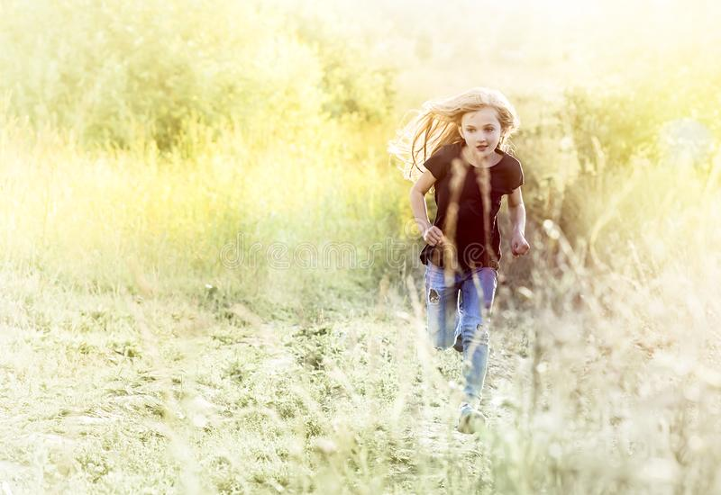 Little girl running on meadow royalty free stock photos