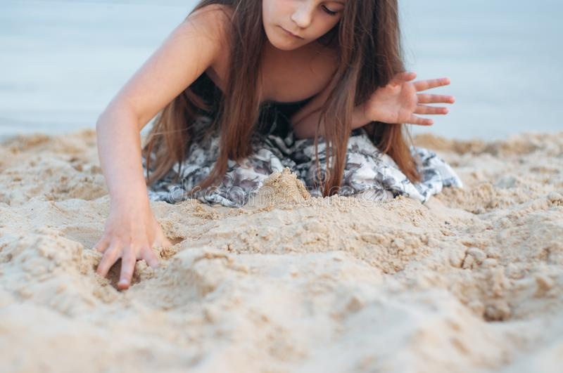 Little girl with long hair in summer dress playing with sand on the beach. Summer, baby, israel, cute, kid, sea, sunscreen, happy, netanya, vacation, beautiful royalty free stock images