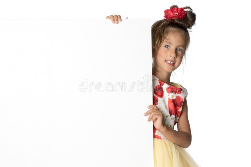 A little girl is looking from behind an empty banner. stock images