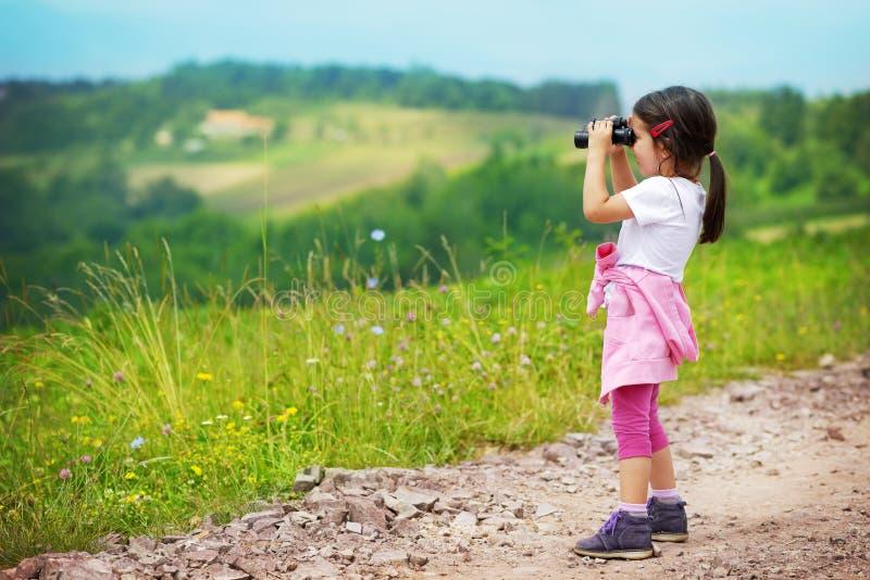 Little girl looking through binoculars outdoor. She is lost. stock image