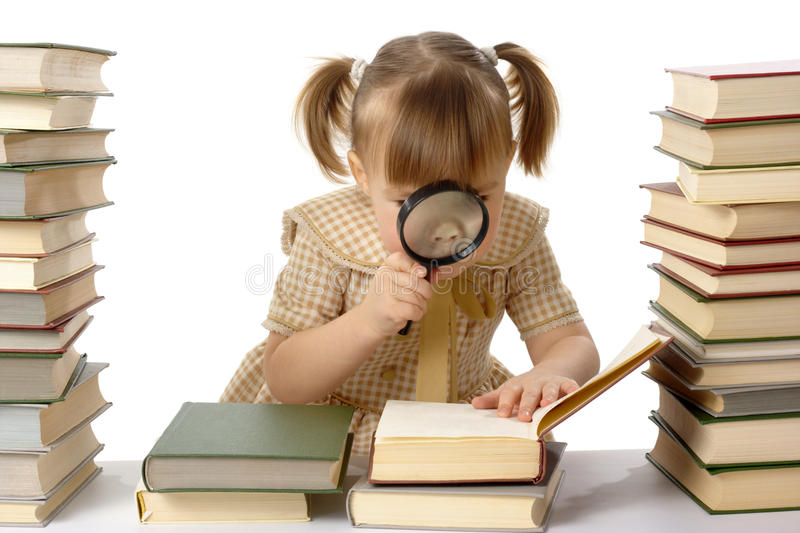 Little girl looking at the book through magnifier stock photos