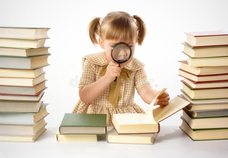 Little girl looking at book through magnifier stock photography