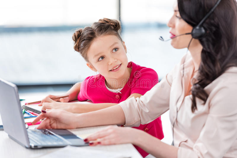 Little girl looking at busy mother in headset working with laptop stock image