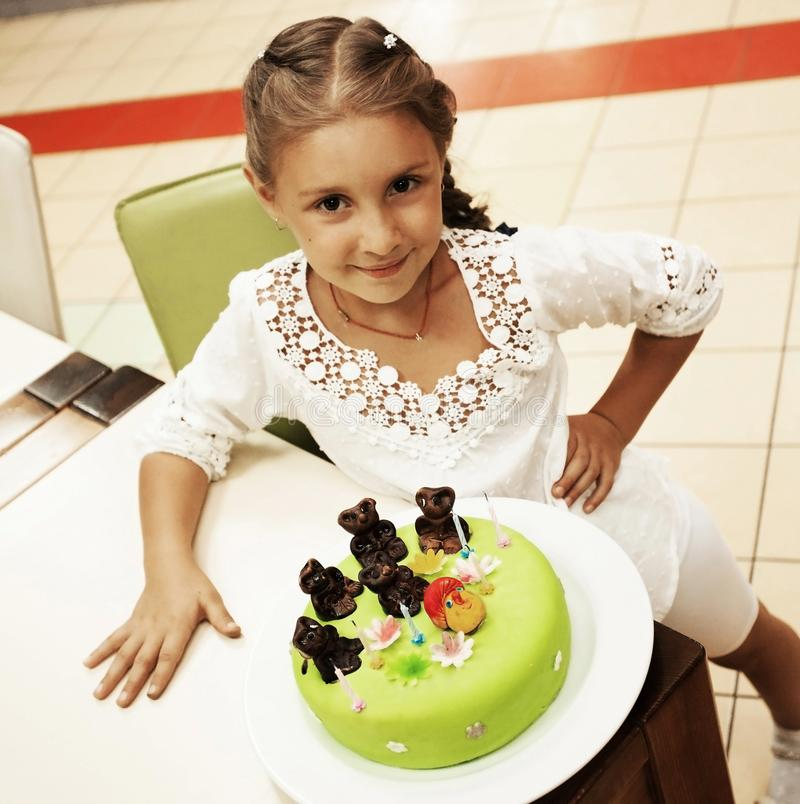 Little girl looking at cake in her birthday stock photo