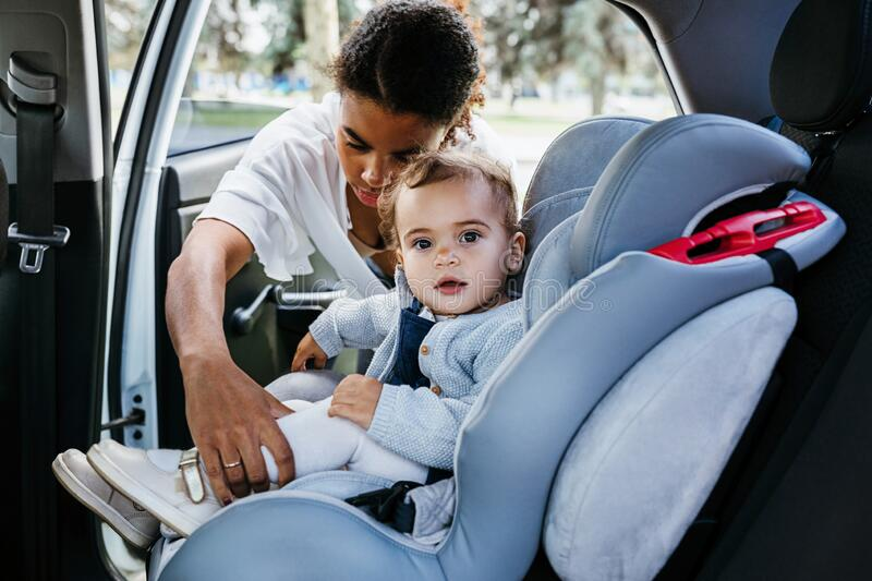 Little girl looking at camera while mother fasten belts stock image