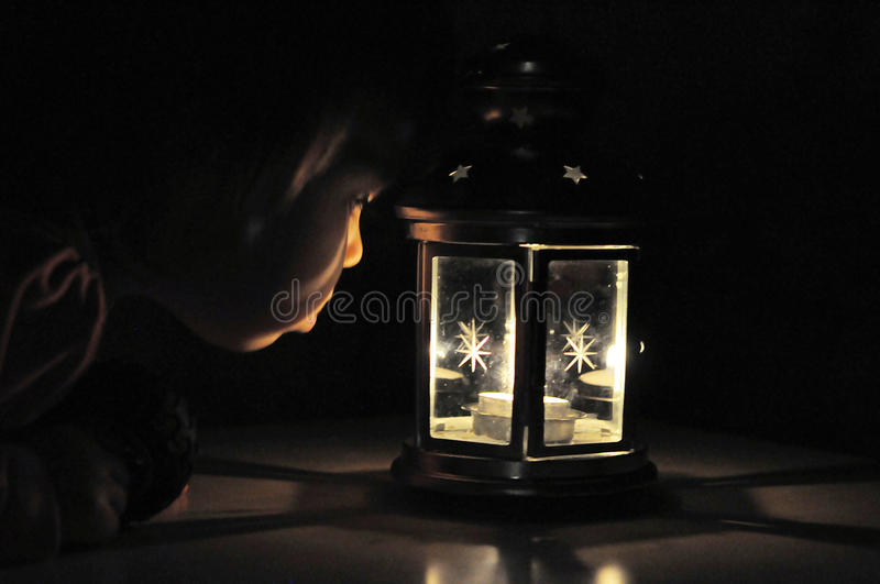 Little girl looking at candle light in lantern, high iso. Shoot,candle light in black background with soft fire stock photos