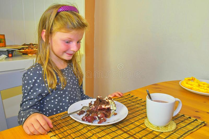 Little girl looking on her birthday cake. Small girl celebrating her six birthday. Little girl is eating cake stock photos