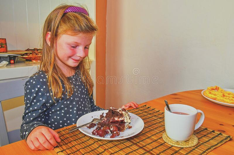 Little girl looking on her birthday cake. Small girl celebrating her six birthday. Birthday cake and little girl. Girl eating birt stock photo