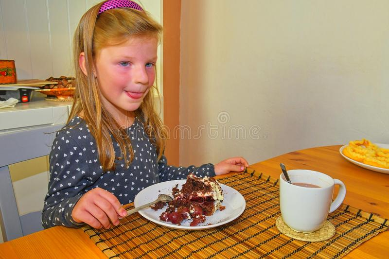 Little girl looking on her birthday cake. Small girl celebrating her six birthday. Little girl is eating cake royalty free stock images