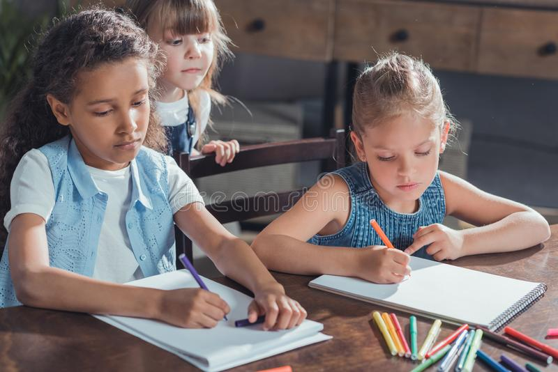 little girl looking how friends drawing pictures with colorful markers stock photos