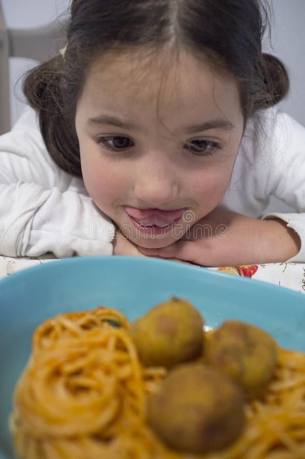 Little girl looking hungry spaghetti with meat balls on plate. Reflections on ice cream counter glasses royalty free stock photo