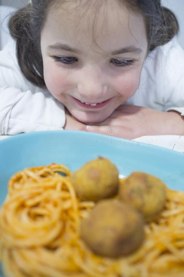 Little girl looking hungry spaghetti with meat balls on plate. Reflections on ice cream counter glasses royalty free stock photos