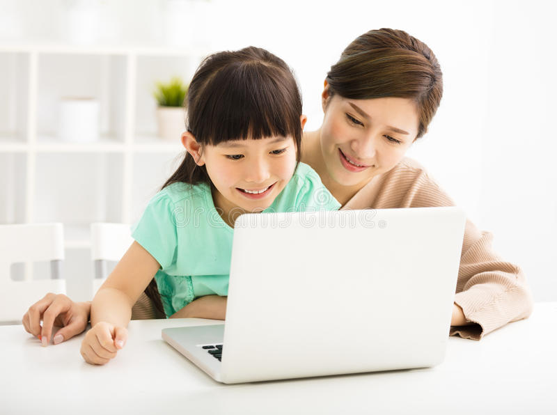 Little girl looking at laptop with her mother stock images