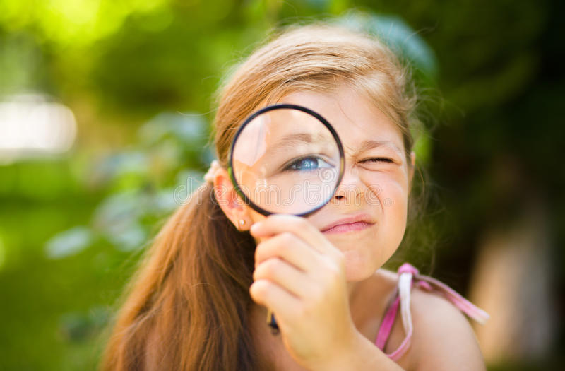 Little girl is looking through magnifier. Outdoor shoot stock photography