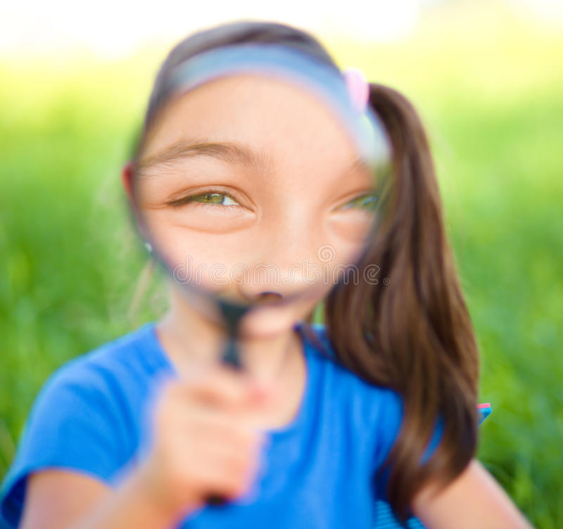 Little girl is looking through magnifier. Outdoor shoot stock images
