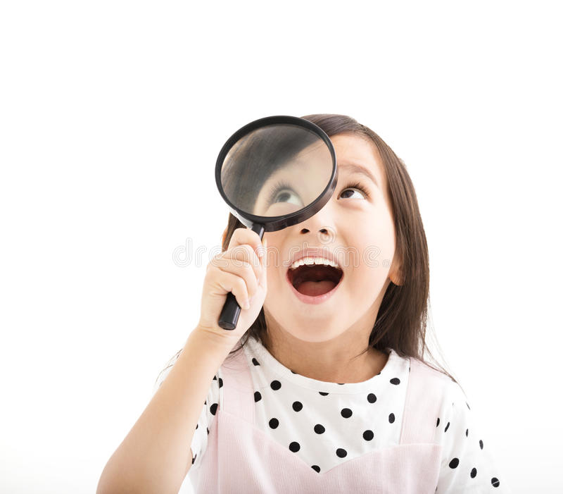 Little girl looking through magnifying glass royalty free stock images