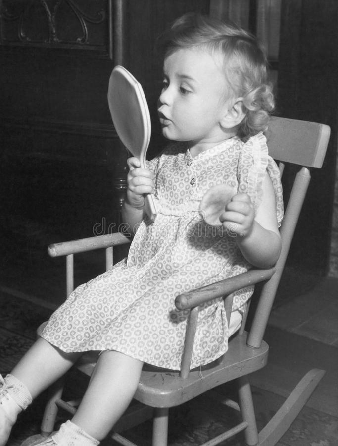 Little girl looking in mirror stock photography