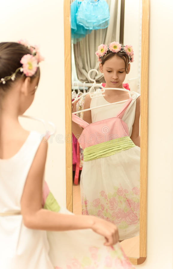 Little girl looking in mirror with new dress in hands stock images