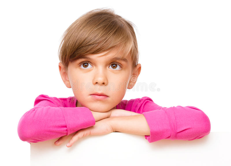 Little girl is looking out from the blank banner. Isolated over white royalty free stock photo