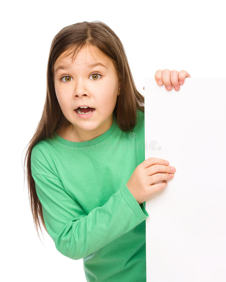 Little girl is looking out from the blank banner. Opening her mouth in astonishment, isolated over white royalty free stock photos