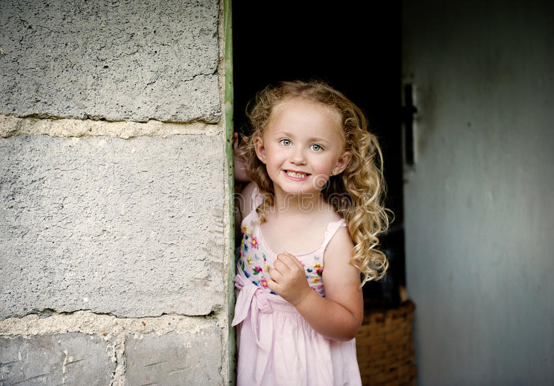 Little girl by the door. Little girl is looking out of the door stock photo