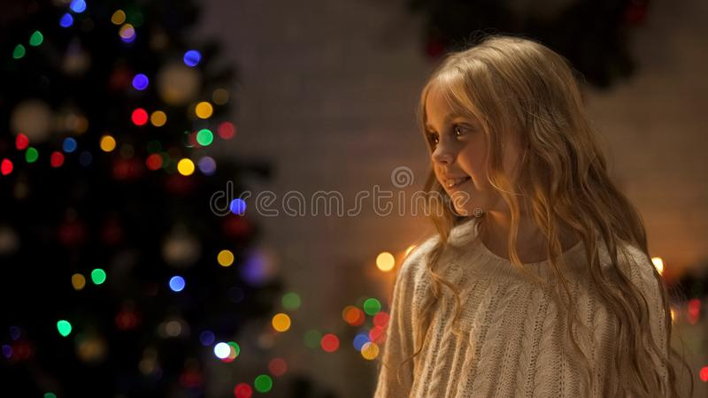 Little girl looking out Santa near glowing Christmas tree, holiday anticipation. Stock photo stock photo