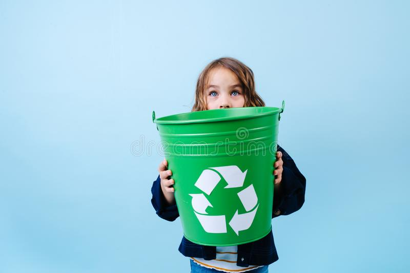 Little girl looking over green recicle bin. Holding in hands. stock images