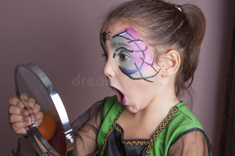 Little girl looking surprised into the mirror royalty free stock photography