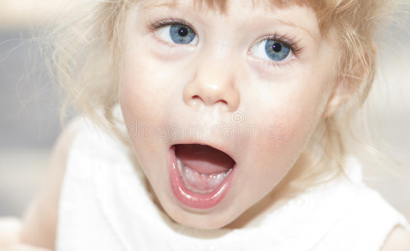 Little girl looking up with her mouth wide open. stock image