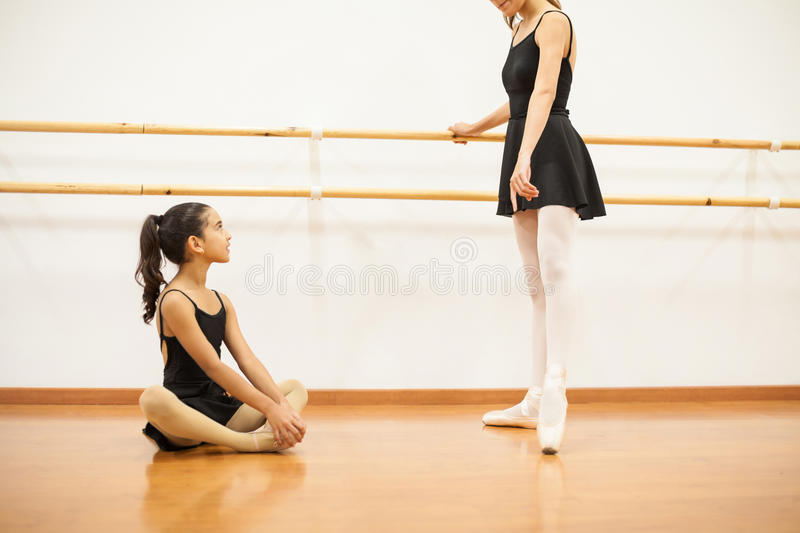 Little girl looking up to her dance teacher stock photography
