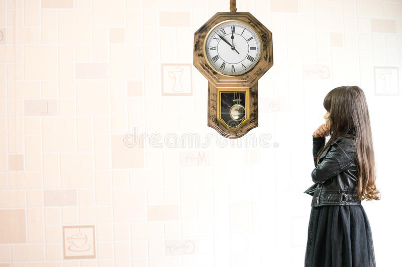 Pretty Child Girl In A Beautiful Black Dress Looking At A Big Yellow Wall  Clock And Counting And Thinking About Time , Ages And Growing