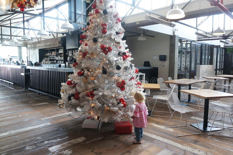 Little girl is looking at white Christmas tree with red present. Box stock photos