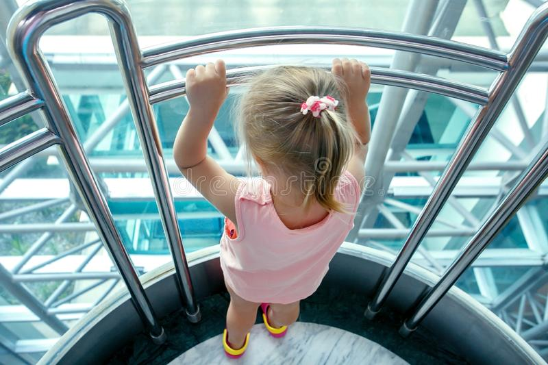 Little girl looking through the window at skyscraper in big city. royalty free stock photo
