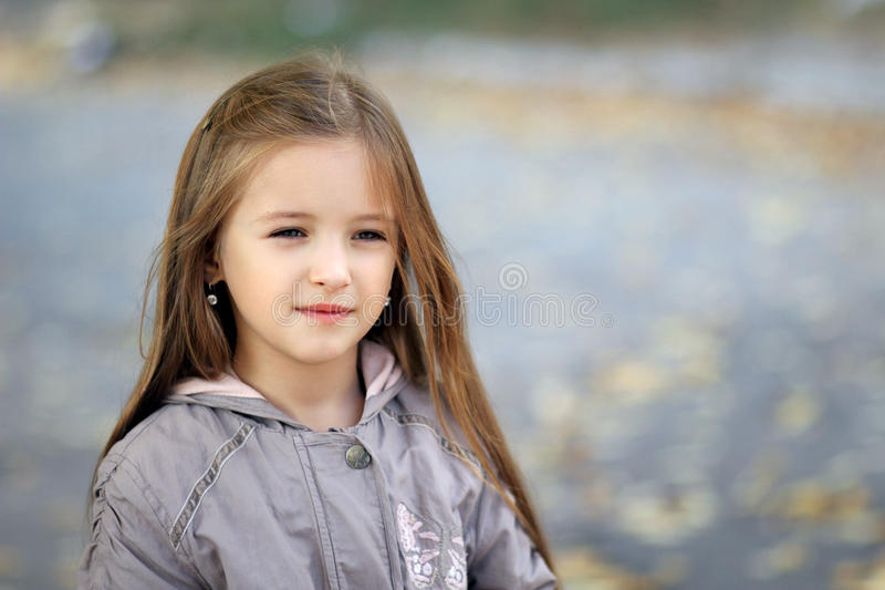 Little girl looks aside in autumn in the park. Beautiful little girl outdoors in the park royalty free stock photo