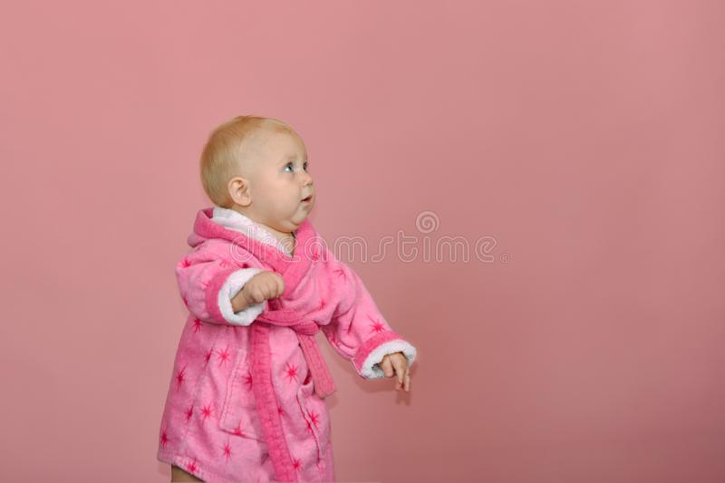 Little girl looks away in a pink bathrobe on a pink background in the studio.  stock photography