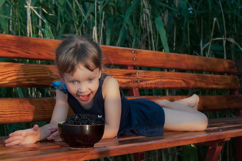 Little girl looks with joy and hapiness at a bowl full of fresh ripe berries. royalty free stock image