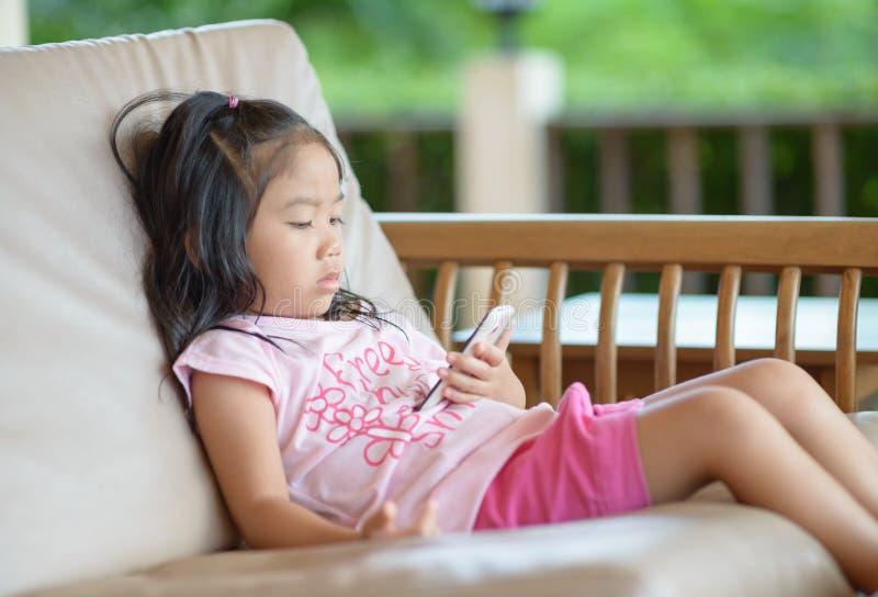 Little girl looks on mobile phone stock photos