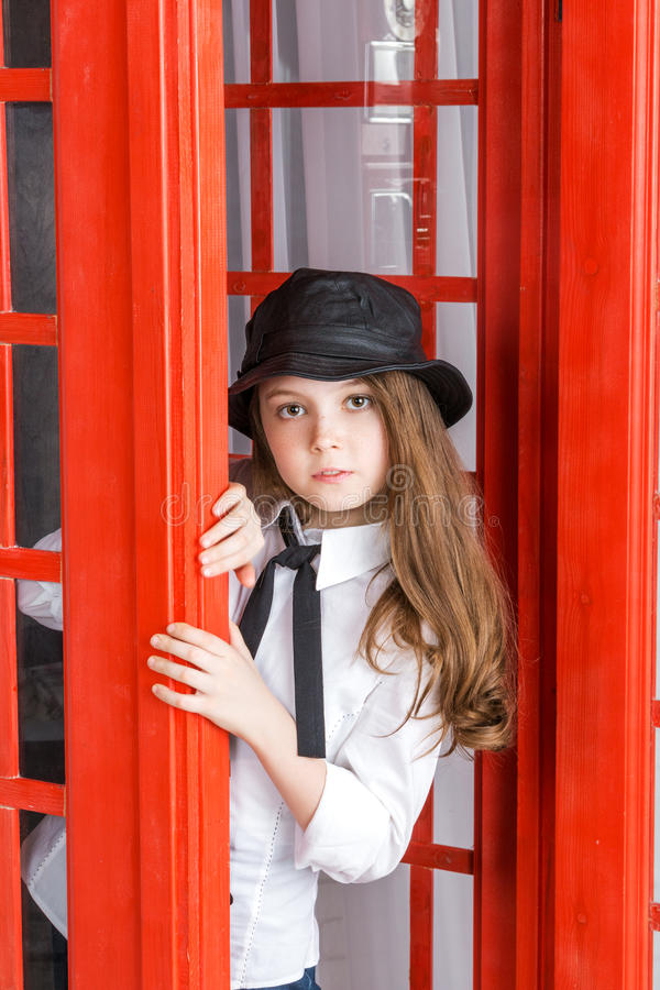 Little girl looks out from a phone booth royalty free stock photography